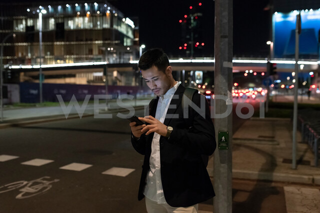 Young businessman on city street at night looking at smartphone, Milan, Italy - CUF47892 - Garage Island Crew/Westend61