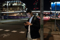 Young businessman on city street at night looking at smartphone, Milan, Italy - CUF47892