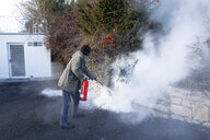 Man extinguishing cable fire in garden near the house - NDF00854