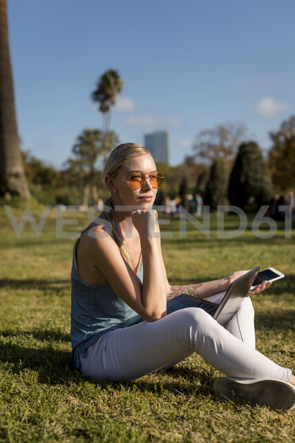 Young woman sitting in park with cell phone and laptop - MAUF02300 - Mauro Grigollo/Westend61