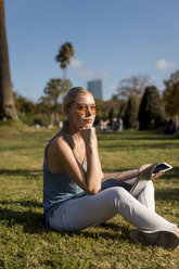 Young woman sitting in park with cell phone and laptop - MAUF02300