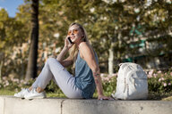 Young woman sitting on a wall talking on cell phone - MAUF02303