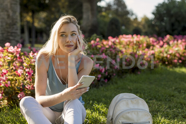 Smiling young woman sitting in park with cell phone and earbuds - MAUF02306