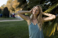 Portrait of happy young woman at a palm tree in park - MAUF02312