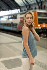 Young woman on cell phone at the train station looking around - MAUF02315