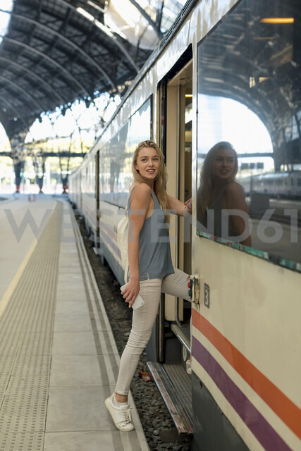 Young woman with cell phone entering a train at the train station - MAUF02318