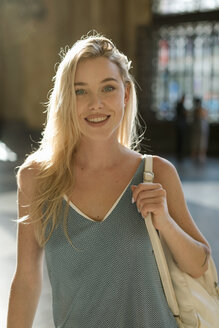 Portrait of smiling young woman in the city - MAUF02321