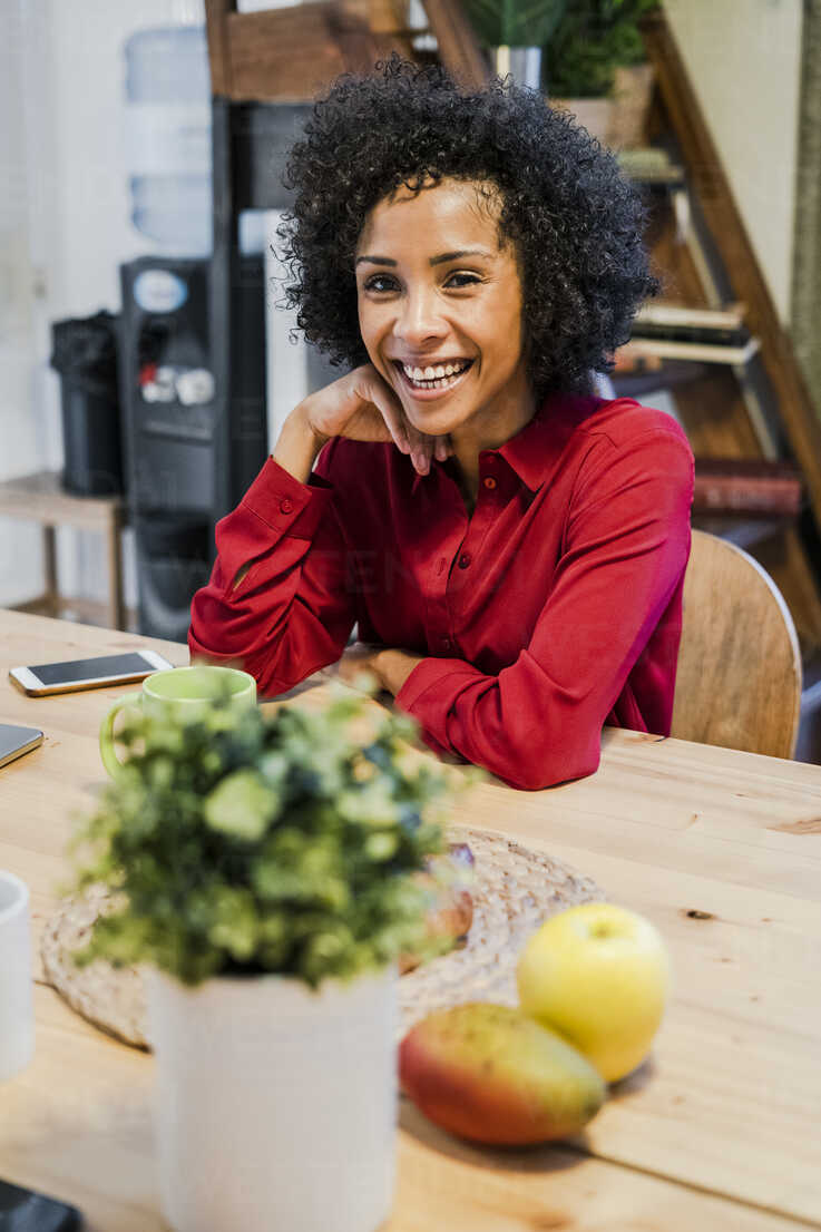 Portrait of happy woman sitting at table - GIOF05482 - Giorgio Fochesato/Westend61