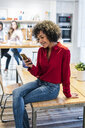 Smiling woman with cell phone sitting on table - GIOF05491