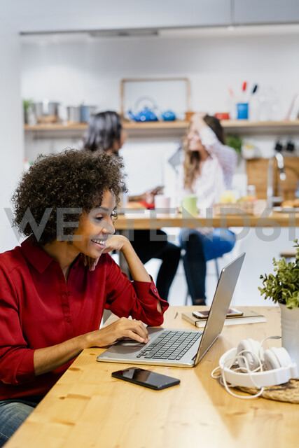 Smiling woman using laptop on table - GIOF05494