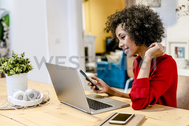 Smiling woman using laptop and cell phone at table - GIOF05497