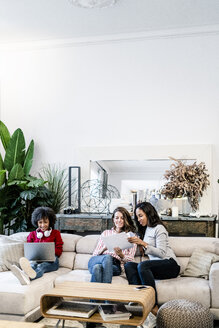 Three women with laptop and documents sitting on couch - GIOF05506