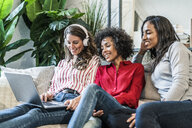 Three happy women with laptop sitting on couch - GIOF05509