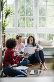 Three women with laptop and documents sitting on the floor at home - GIOF05521