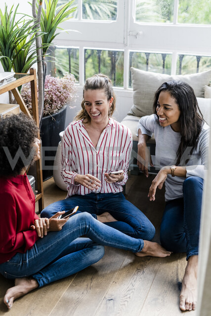 Three happy women sitting on the floor at home with cell phones - GIOF05527 - Giorgio Fochesato/Westend61