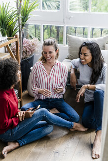 Three happy women sitting on the floor at home with cell phones - GIOF05527