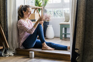 Smiling woman sitting on the floor at home with cell phone - GIOF05530