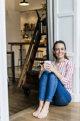Portrait of smiling woman sitting on the floor at home with cup of coffee - GIOF05533