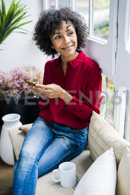 Smiling woman sitting at the window at home with cell phone - GIOF05536
