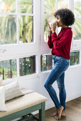 Woman looking out of window at home drinking cup of coffee - GIOF05539