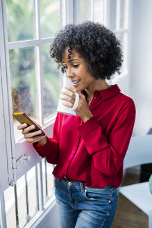 Woman with cup of coffee and cell phone standing at the window at home - GIOF05542