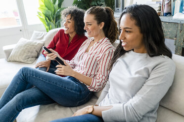 Three happy women sitting on couch at home watching Tv - GIOF05545