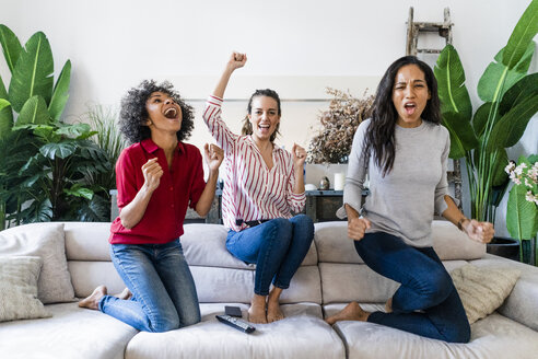 Three excited women on couch at home watching Tv and cheering - GIOF05548