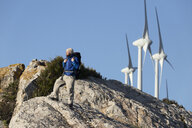 Spain, Andalusia, Tarifa, man on a hiking trip standing on rock with wind turbines in background - KBF00416