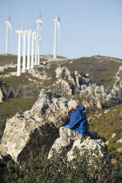 Spain, Andalusia, Tarifa, man on a hiking trip sitting on rock with wind turbines in background - KBF00419
