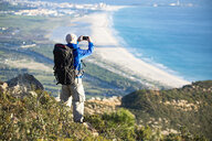Spain, Andalusia, Tarifa, man on a hiking trip at the coast taking a cell phone picture - KBF00425
