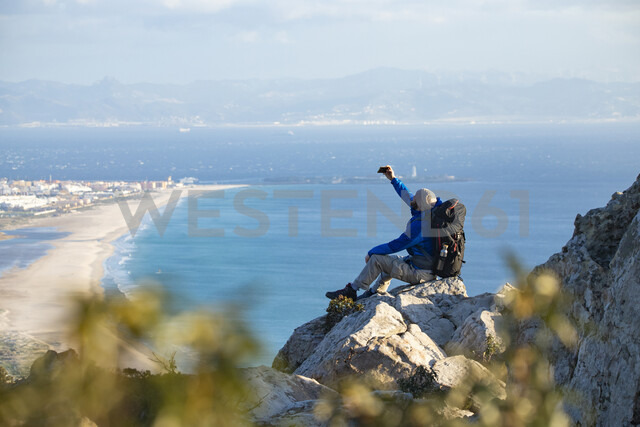 Spain, Andalusia, Tarifa, man on a hiking trip at the coast sitting on a rock taking a selfie - KBF00428