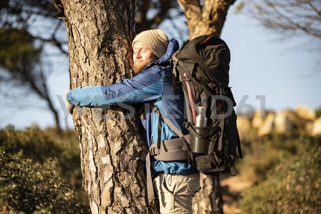 Man on a hiking trip hugging a tree - KBF00431