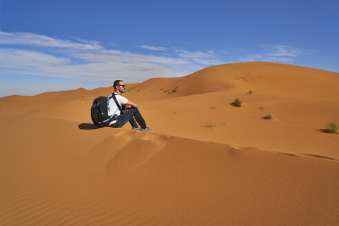 Morocco, man sitting on desert dune looking at view - EPF00546