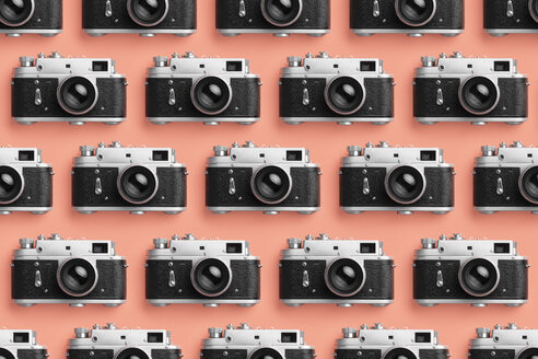 Classic photo cameras organized in a row over coral color background - DRBF00128