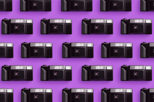 Classic plastic photo cameras organized in a row over pink background - DRBF00131