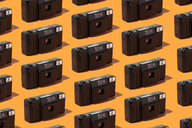 Classic plastic photo cameras organized in a row over orange background - DRBF00134