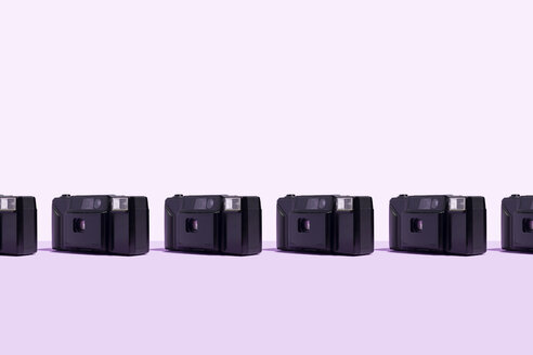 Classic plastic photo cameras organized in a row over purple background - DRBF00137