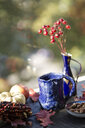 Self-made blue clay mug on autumnal decorated window sill - JESF00207