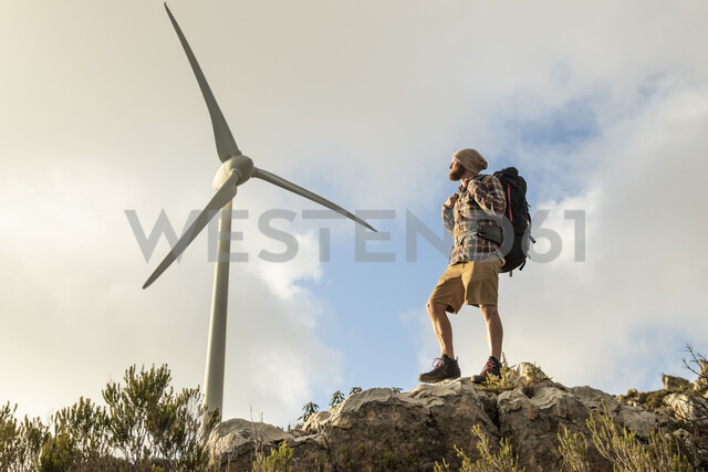 Spain, Andalusia, Tarifa, man on a hiking trip standing on rock with wind turbine in background - KBF00436