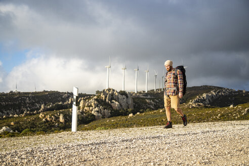 Spain, Andalusia, Tarifa, man on a hiking trip walking on dirt road with wind turbines in background - KBF00439