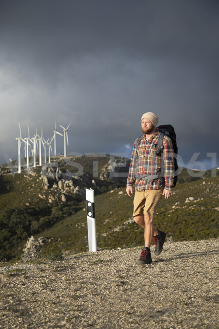 Spain, Andalusia, Tarifa, man on a hiking trip walking on dirt road with wind turbines in background - KBF00442