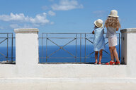 Two girls in sun hats looking out to sea from wall,  Erice, Sicily, Italy - CUF47894