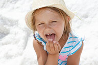 Girl in sun hat licking her fingers on beach, portrait Trapani, Sicily, Italy - CUF47897