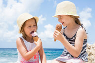 Two girls eating ice cream cone on beach, Scopello, Sicily, Italy - CUF47900