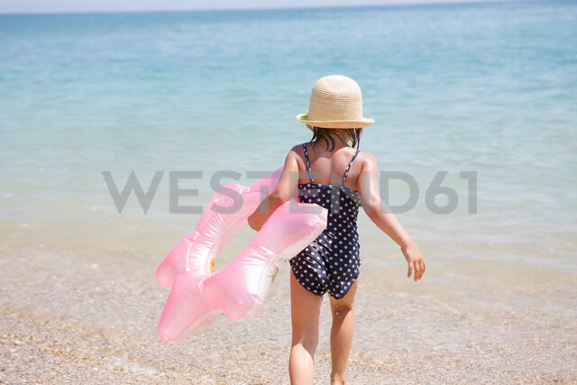 Girl carrying pink inflatable into sea, Scopello, Sicily, Italy - CUF47903