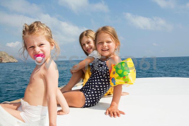 Three cute girls sitting on boat, portrait, Castellammare del Golfo, Sicily, Italy - CUF47906