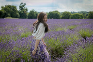 Mid adult woman with long brown hair looking over her shoulder in lavender field, portrait - CUF47909