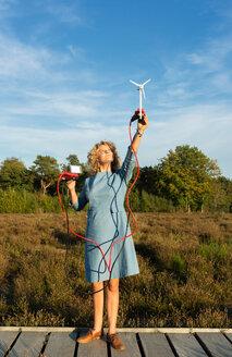 Teenage girl powering LED light using miniature wind turbine, Netherlands - CUF47936