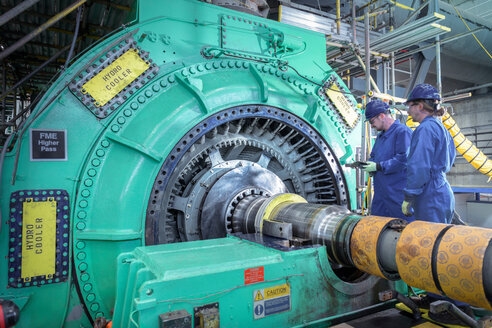 Engineers inspecting generator in nuclear power station during outage - CUF47951