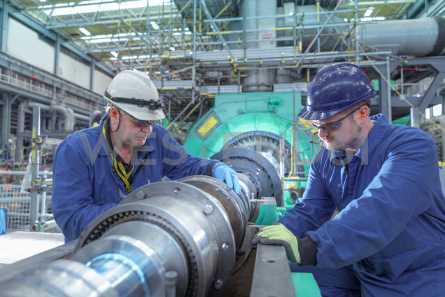 Engineers inspecting gears at generator end in nuclear power station during outage - CUF47954